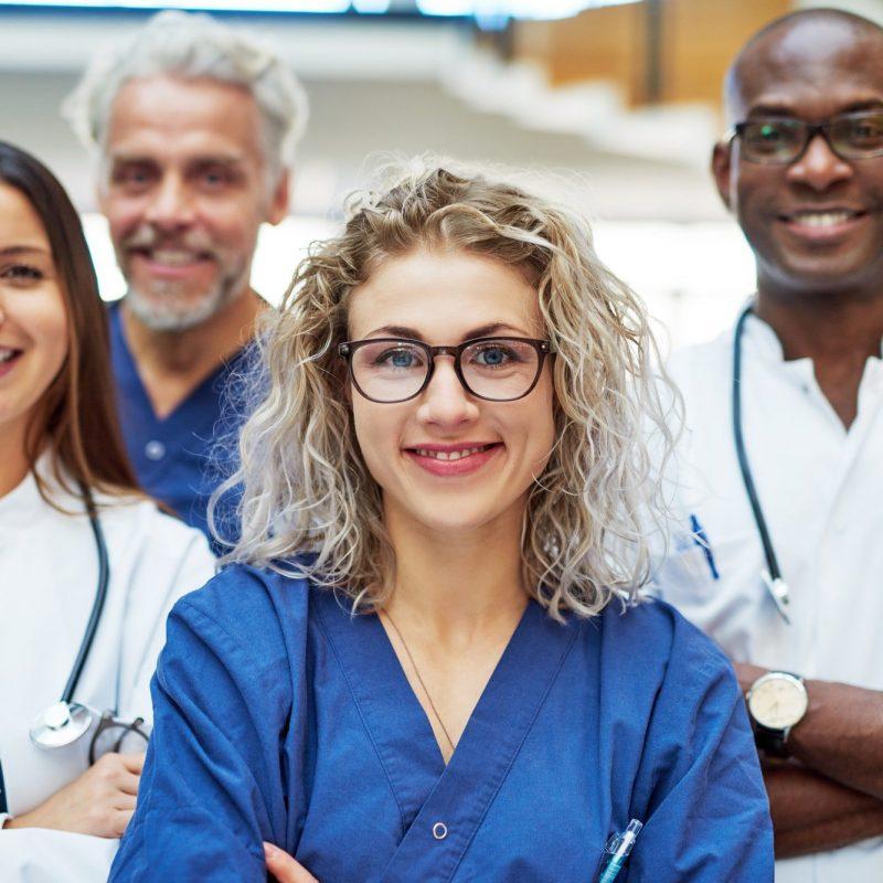 Cheerful medics looking at camera in clinic